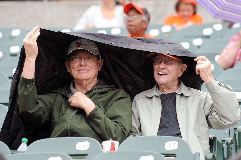 . Fans cover from the rain before a baseball game between the Baltimore Orioles and the Colorado Rockies on August 18, 2013 at Oriole Park at Camden Yards in Baltimore, Maryland.  (Photo by Mitchell Layton/Getty Images)