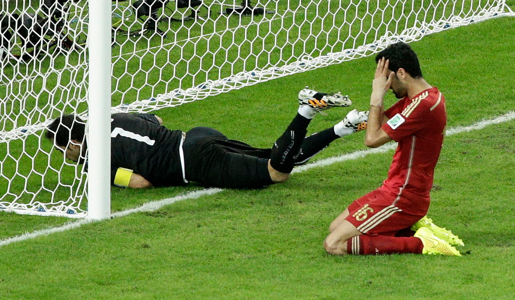 . Spain\'s Sergio Busquets, right, holds his head after failing to score past Chile\'s goalkeeper Claudio Bravo during the group B World Cup soccer match between Spain and Chile at the Maracana Stadium in Rio de Janeiro, Brazil, Wednesday, June 18, 2014.  (AP Photo/Christophe Ena)