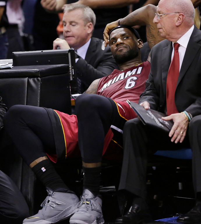 . Miami Heat forward LeBron James (6) sits on the bench after injuring himself against the San Antonio Spurs during the second half in Game 1 of the NBA basketball finals on Thursday, June 5, 2014 in San Antonio. (AP Photo/Eric Gay)