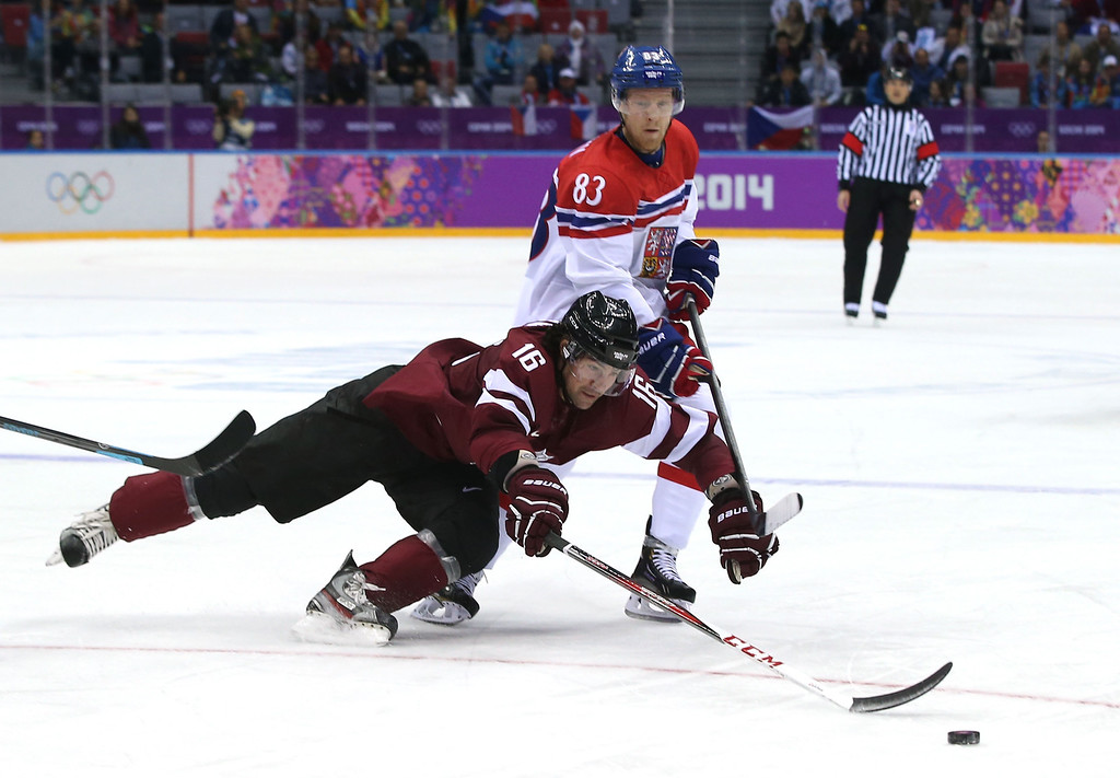 . Kaspars Daugavins #16 of Latvia dives for a puck against Ales Hemsky #83 of Czech Republic in the second period during the Men\'s Ice Hockey Preliminary Round Group C game on day seven of the Sochi 2014 Winter Olympics at Bolshoy Ice Dome on February 14, 2014 in Sochi, Russia.  (Photo by Bruce Bennett/Getty Images)