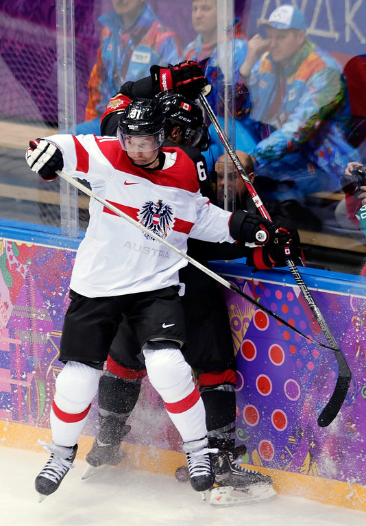 . Shea Weber (behind) of Canada fights for the puck with Oliver Setzinger (front) of Austria during the match between Canada and Austria at the Bolshoy Ice dom in the Ice Hockey tournament at the Sochi 2014 Olympic Games, Sochi, Russia, 14 February 2014.  EPA/ANATOLY MALTSEV