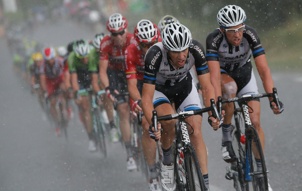. The pack rides in a downpour during the fifteenth stage of the Tour de France cycling race over 222 kilometers (137.9 miles) with start in Tallard and finish in Nimes, France, Sunday, July 20, 2014. (AP Photo/Christophe Ena)