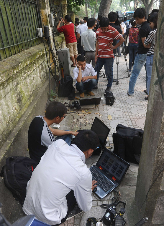 . Reporters from local online newspapers work on lapop computers outside the residence of late general Vo Nguyen Giap in Hanoi on October 6, 2013. As news emerged of the death of Vietnam\'s legendary General Vo Nguyen Giap, most journalists were forced to stay silent -- leaving the landmark event to be revealed by the country\'s swelling ranks of Internet users. HOANG DINH NAM/AFP/Getty Images