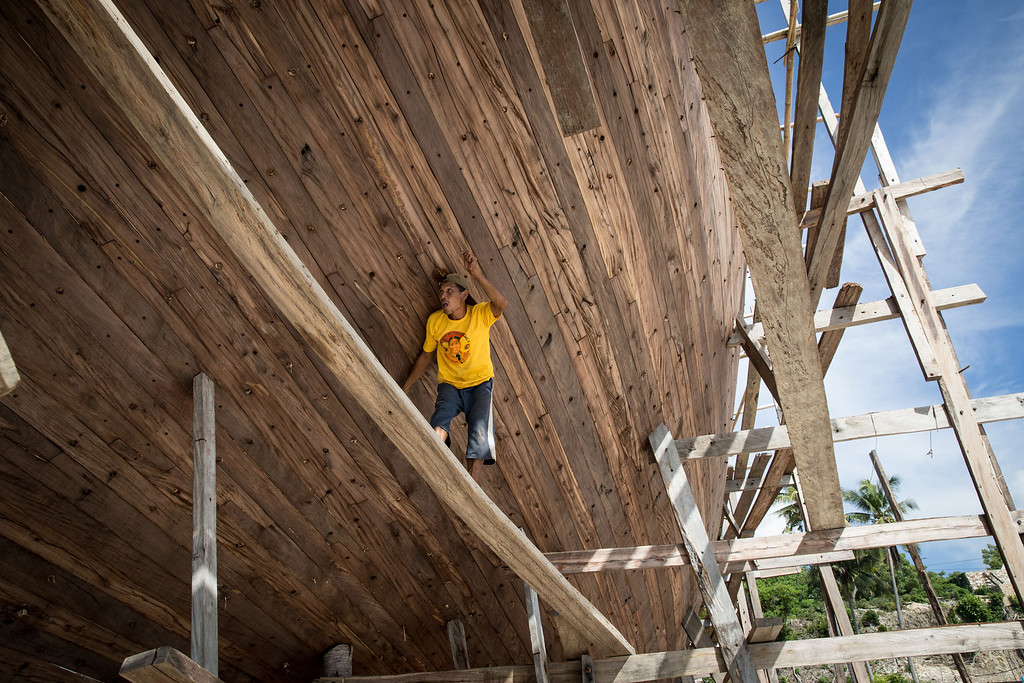 . A Buginese man works as he make sure the hull of phinisi at Tanjung Bira Beach on May 2, 2014 in Bulukumba, South Sulawesi, Indonesia.  (Photo by Agung Parameswara/Getty Images)
