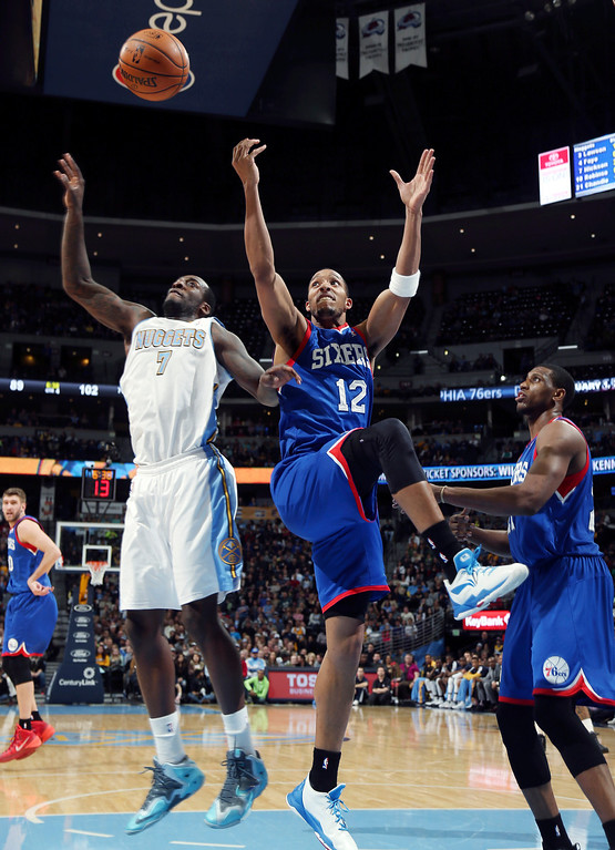 . Denver Nuggets forward J.J. Hickson, left, fights for control of a rebound with Philadelphia 76ers forward Evan Turner, center, as forward Thaddeus Young stands near in the fourth quarter of the Sixers\' 114-102 victory in an NBA basketball game in Denver on Wednesday, Jan. 1, 2014. (AP Photo/David Zalubowski)