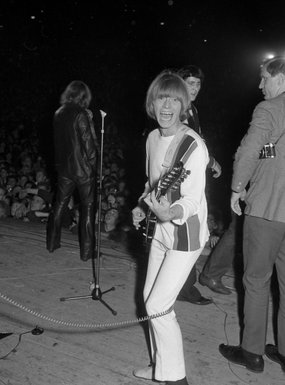 """. Brian Jones, guitarist of the Rock Band The Rolling Stones, strikes a pose with wide open mouth, during the band\'s concert at the \""""Waldbuehne\"""" (Forest Stage) in West Berlin, West Germany, September 15, 1965. (AP Photo)"""