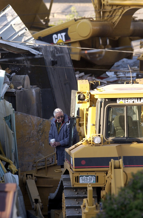 . (l-r) Investigators  examine  the fortified bulldozer  driven by Marvin Heemeyer where it came to rest at Gambles of Grand County on highway 40 in Granby, CO. Heemeyer drove a fortified bulldozer through the streets of Granby Friday destroying a number of buildings.   (DENVER POST PHOTO BY HYOUNG CHANG)