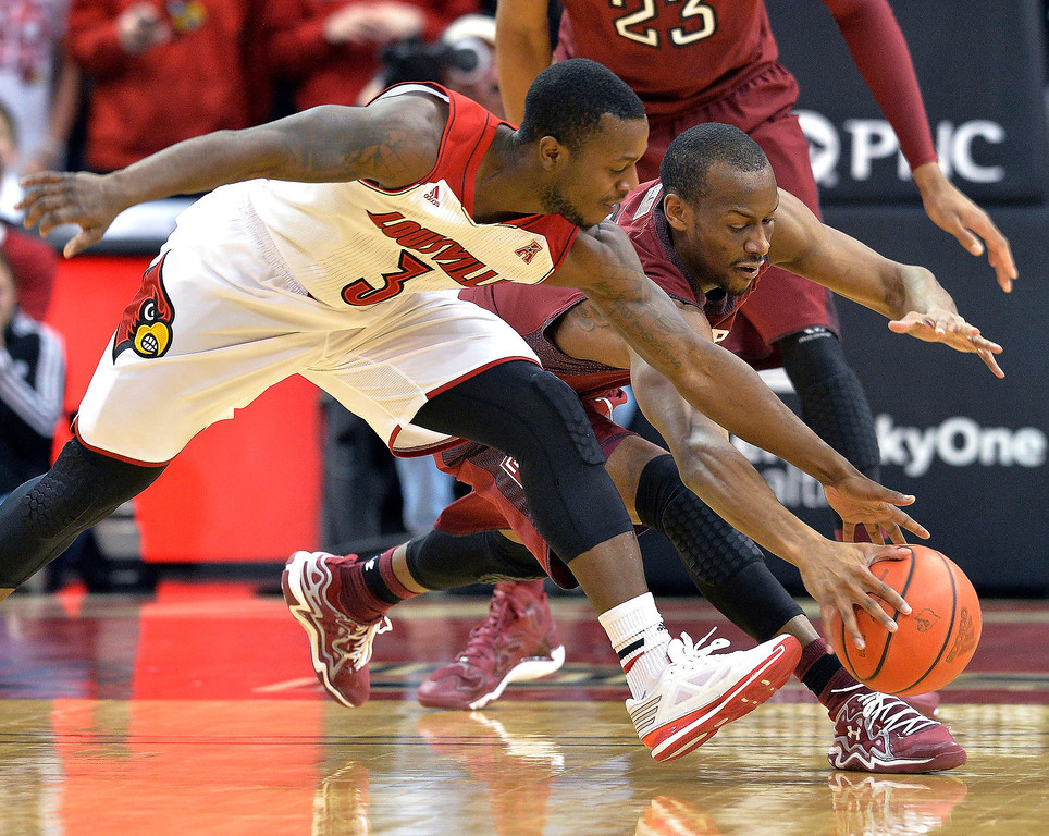 . Louisville\'s Chris Jones, front, and Temple\'s Will Cummings reach for a loose ball during the first half of an NCAA college basketball game, Thursday, Feb. 27, 2014, in Louisville, Ky. (AP Photo/Timothy D. Easley)