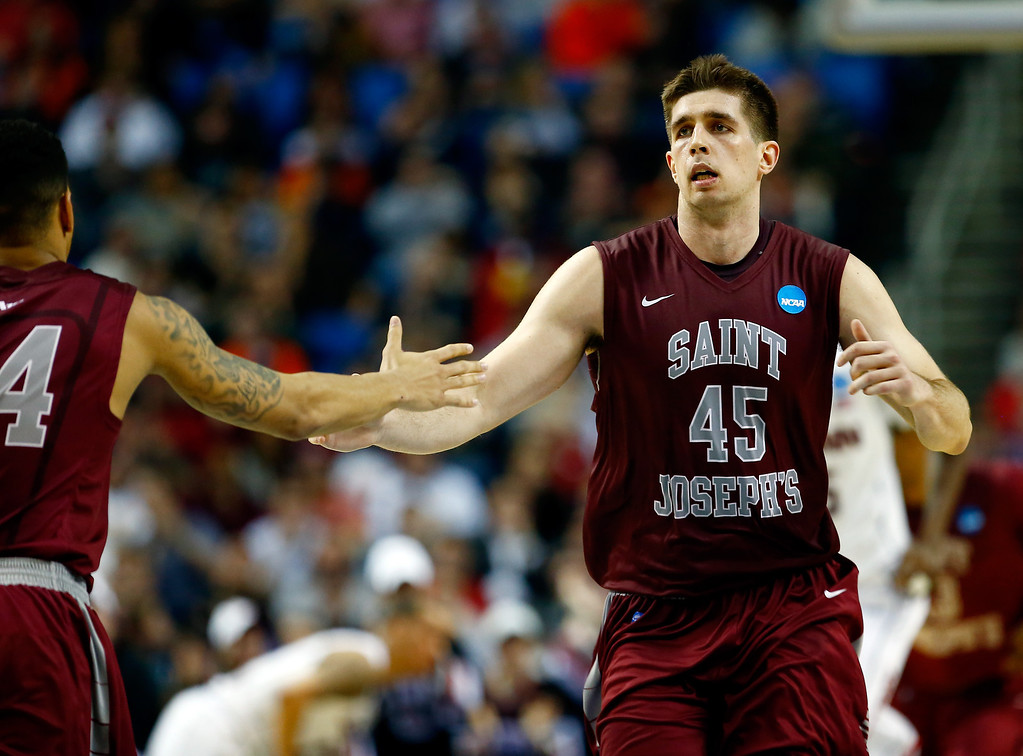 . BUFFALO, NY - MARCH 20: Halil Kanacevic #45 celebrates with Chris Wilson #24 of the Saint Joseph\'s Hawks against the Connecticut Huskies during the second round of the 2014 NCAA Men\'s Basketball Tournament at the First Niagara Center on March 20, 2014 in Buffalo, New York.  (Photo by Jared Wickerham/Getty Images)