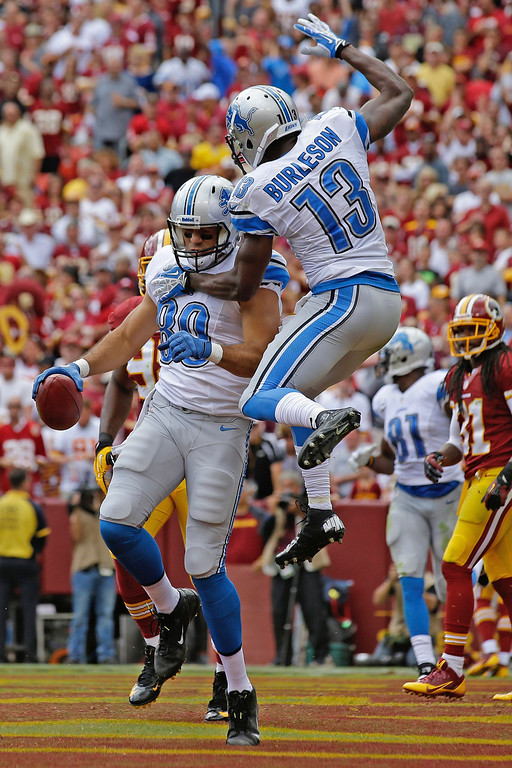 . Detroit Lions tight end Joseph Fauria celebrates his touchdown reception with wide receiver Nate Burleson (13) during the first half of a NFL football game against the Washington Redskins in Landover, Md., Sunday, Sept. 22, 2013. (AP Photo/Alex Brandon)