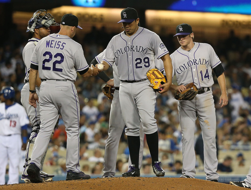 . Pitcher Jorge De La Rosa #29 of the Colorado Rockies hands the ball to manager Walt Weiss #22 in the fourth inning during a pitching change in their MLB game against the Los Angeles Dodgers at Dodger Stadium on June 18, 2014 in Los Angeles, California.  (Photo by Victor Decolongon/Getty Images)