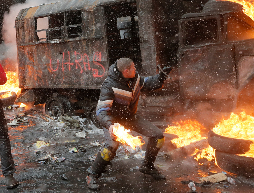 . A protester throws a Molotov cocktail during clashes with police in central Kiev, Ukraine, Wednesday, Jan. 22, 2014.  (AP Photo/Efrem Lukatsky)