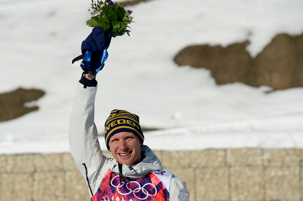 . Bronze medalist Sweden\'s Daniel Richardsson celebrates on the podium in the Men\'s Cross-Country Skiing 15km Classic Flower Ceremony at the Laura Cross-Country Ski and Biathlon Center during the Sochi Winter Olympics on February 14, 2014 in Rosa Khutor near Sochi. AFP PHOTO / KIRILL KUDRYAVTSEV/AFP/Getty Images