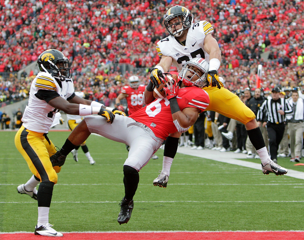 . Iowa defensive backs Desmond King, left, and John Lowdermilk, right, break up a pass intended for Ohio State wide receiver Evan Spencer, center, during the second quarter of an NCAA college football game Saturday, Oct. 19, 2013, in Columbus, Ohio. (AP Photo/Jay LaPrete)