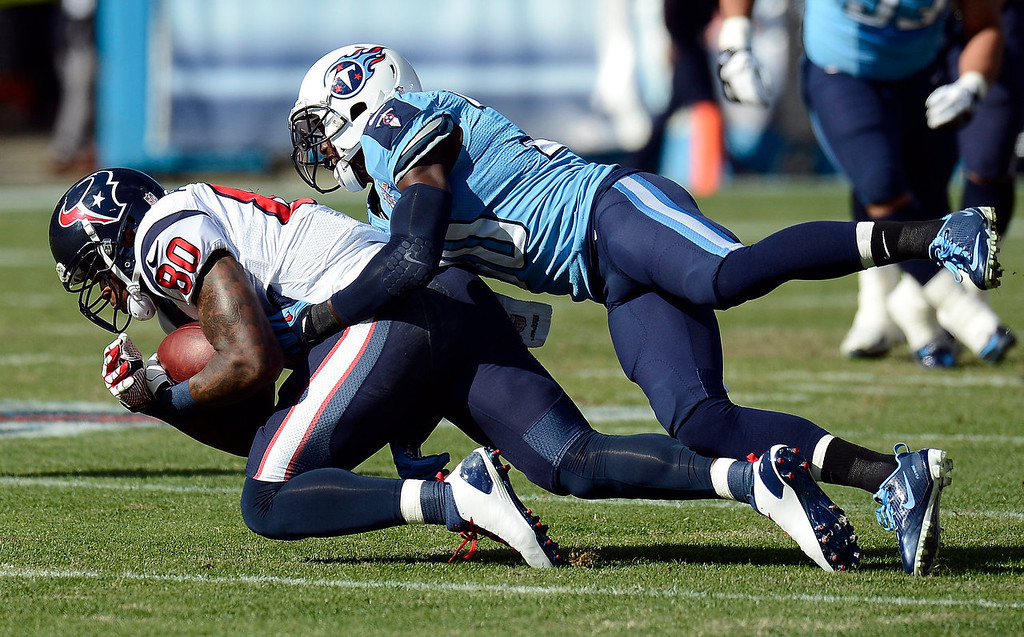 . Houston Texans wide receiver Andre Johnson (80) is brought down by Tennessee Titans cornerback Jason McCourty after Johnson gained 13-yards in the first quarter of an NFL football game Sunday, Dec. 29, 2013, in Nashville, Tenn. (AP Photo/Mark Zaleski)