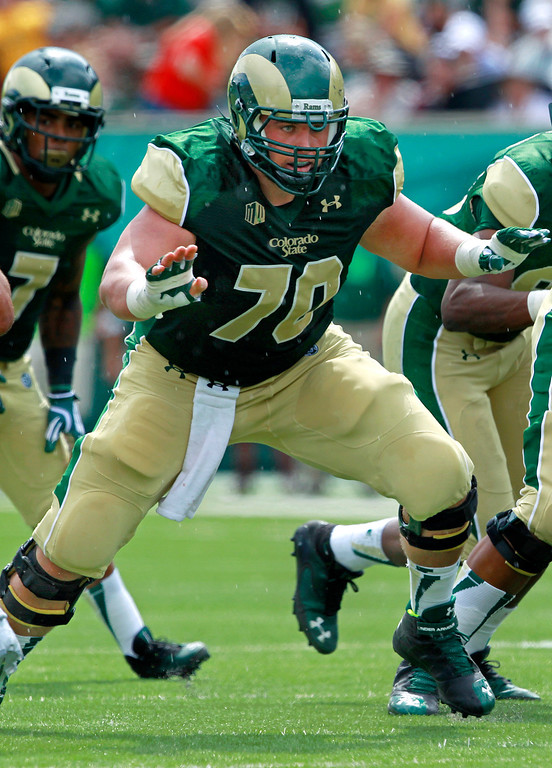 . Colorado State center Weston Richburg, center, looks to block against Cal Poly in the second quarter of a college football game in Fort Collins, Colo., on Saturday, Sept. 14, 2013. (AP Photo/David Zalubowski)