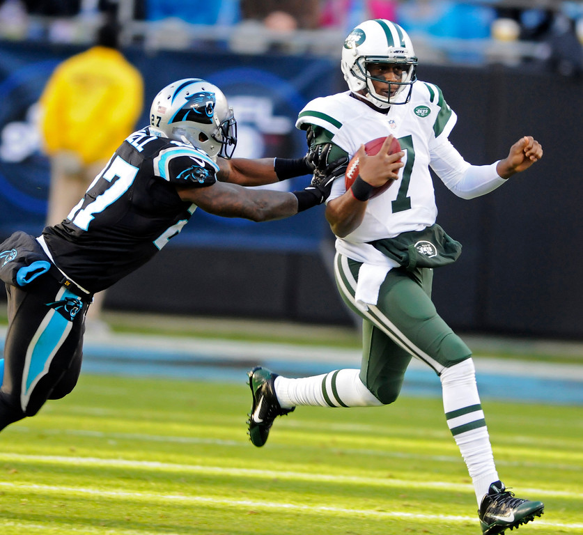 . New York Jets quarterback Geno Smith (7) is pushed out of bounds by Carolina Panthers\' Quintin Mikell (27) during the first half of an NFL football game in Charlotte, N.C., Sunday, Dec. 15, 2013. (AP Photo/Mike McCarn)