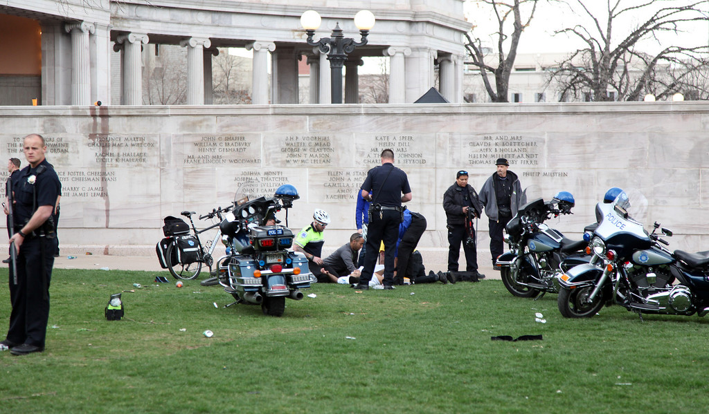 . Denver, CO. - April 20: Denver Paramedics and Denver Police officers attend to a shooting victim at Civic Center Park in Denver Colorado, Saturday April 20th, 2013 after a 4/20 pot rally. Two people were shot during Saturday\'s annual 4/20 marijuana rally, held on a day cannabis enthusiasts regard as a holiday called 4/20 drew tens of thousands to Denver\'s Civic Center park. This is the first 4/20 marijuana rally since Colorado voters legalized marijuana use for people 21 and older in November. (Photo By Alex Scott/Special to The Denver Post)