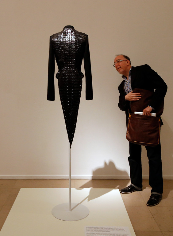 ". A visitor looks at ""Swallow-tailed jacket of wool cloth and crocodile\"" of Haute Couture Spring Summer 2003 collections by French Tunisian born Fashion designer Azzedine Alaia, presented for the first Paris retrospective of couturier at the Museum of Modern Art in Paris, Wednesday, Sept. 25, 2013. A selection of seventy iconic models retracing a unique creative career of Alaia are displayed for the reopening of the Galliera Museum and in the Matisse room at the Museum of Modern Art of Paris. (AP Photo/Francois Mori)"