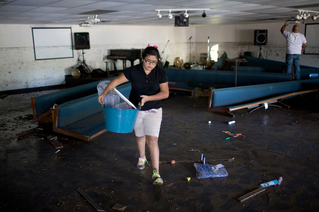 . Volunteers clean up the First Independent Baptist Church after heavy rains caused water levels to rise over four feet in the church before receding on Thursday Oct. 31, 2013 in Austin, Texas. The National Weather Service said more than a foot of rain fell in Central Texas. (AP Photo/ Tamir Kalifa)