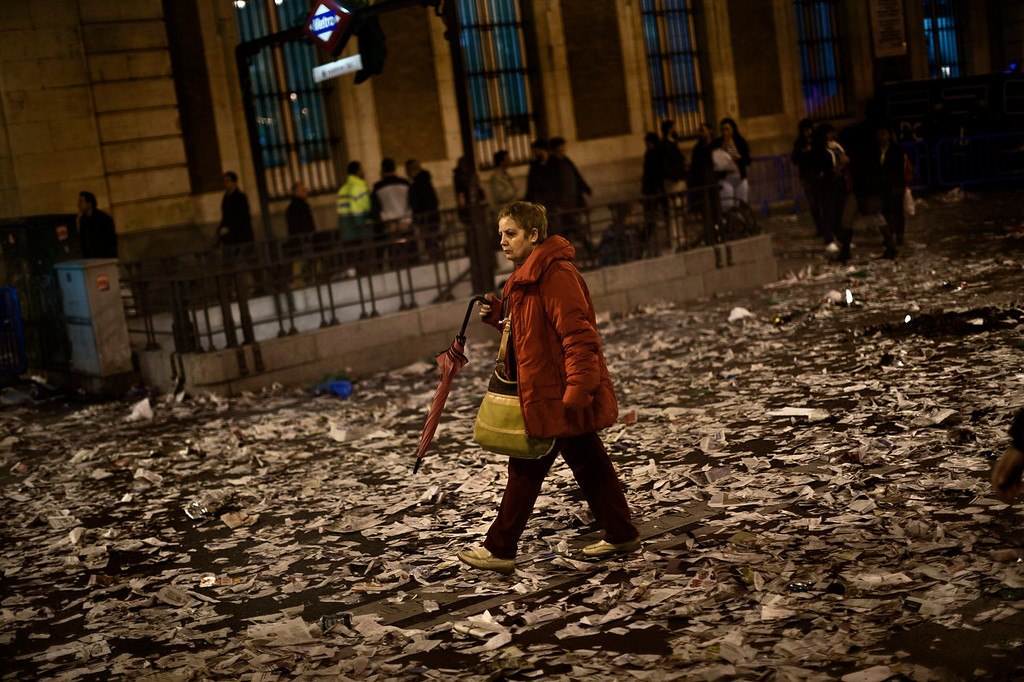 . A woman walks trough a trash covered street after a demonstration against layoffs of street cleaners and garbage collectors in Madrid, Spain, Monday, Nov. 4, 2013. Trash collectors in Madrid have started bonfires and set off firecrackers during a noisy protest in one of the Spanish capitalís main squares as they prepare to start an open-ended strike. Hundreds of street cleaners and garbage collectors who work in the cityís public parks converged on the Puerta del Sol plaza late Monday. (AP Photo/Daniel Ochoa de Olza)