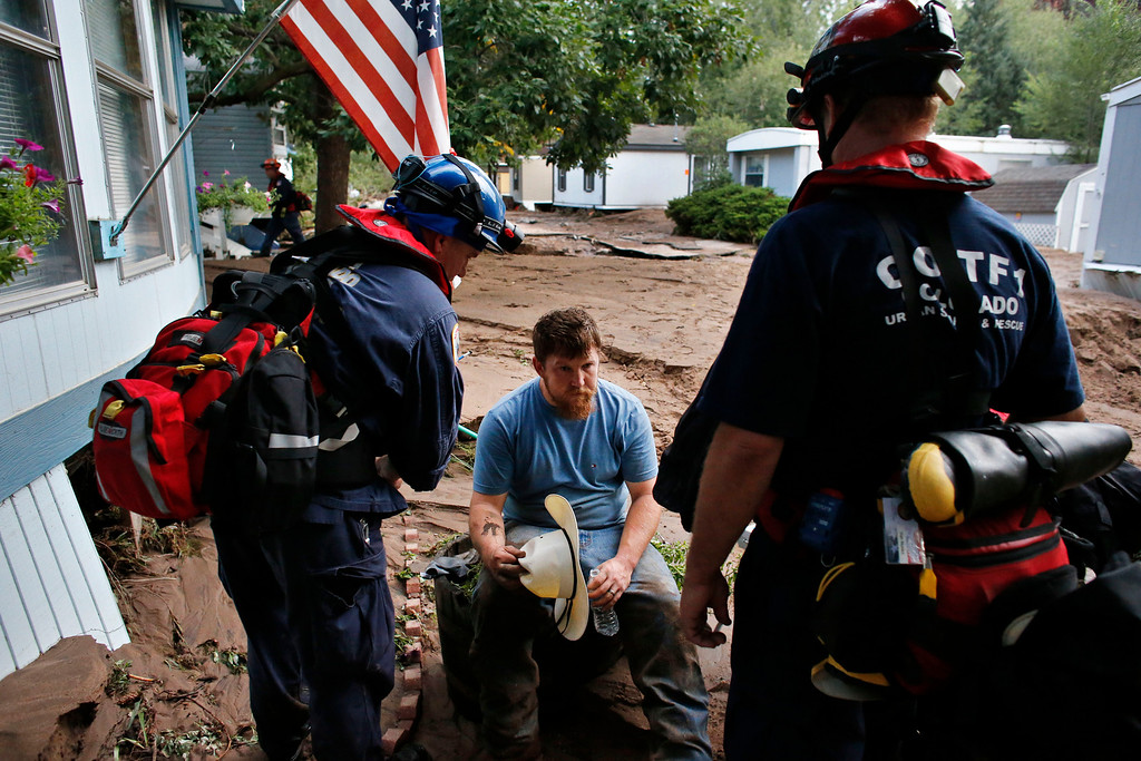. Suffering from dehydration, local resident Fred Rob gets help from emergency responders after floods left homes and infrastructure in a shambles, in Lyons, Colo., Friday Sept. 13, 2013. (AP Photo/Brennan Linsley)