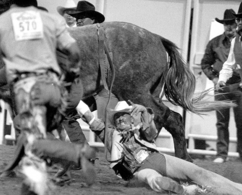 . Danny K. Green gets taken for a ride as he couldn\'t get his hand loose from a fierce horse called Ten below. Danny Green is from Meda, Arizpna. Other cowboys coming to his rescue. This was in the Bareback Bronc Riding to open the 1991 Rodeo season. John Leyba, The Denver Post