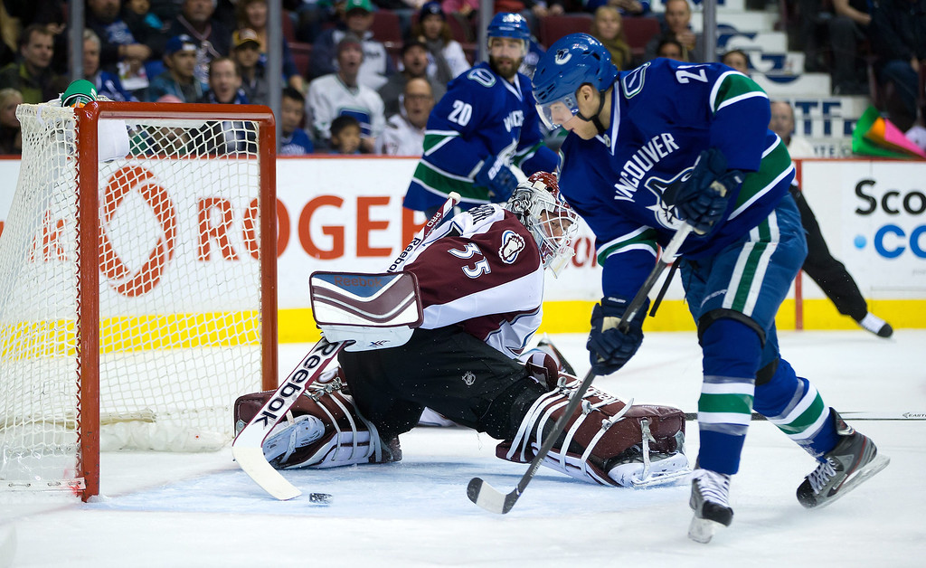 . Vancouver Canucks\' Mike Santorelli, right, scores a goal against Colorado Avalanche goalie Jean-Sebastien Giguere during first period NHL hockey game in Vancouver, British Columbia on Sunday, Dec. 8, 2013. (AP Photo/The Canadian Press, Darryl Dyck)