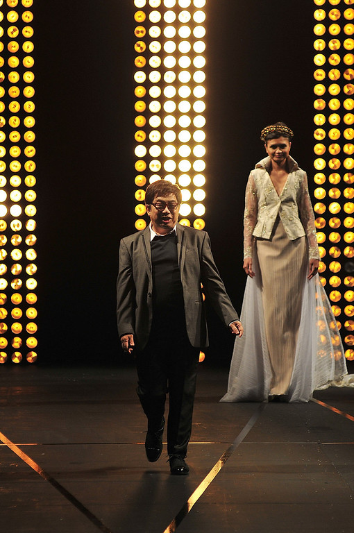 . Filipino designer Albert Andrada bows to the audience as a model looks on to conclude the 2013 Philippine Fashion Week Holiday at the SMX convention center in Pasay CIty on May 26, 2013 in Manila, Philippines.  (Photo by Veejay Villafranca/Getty Images)