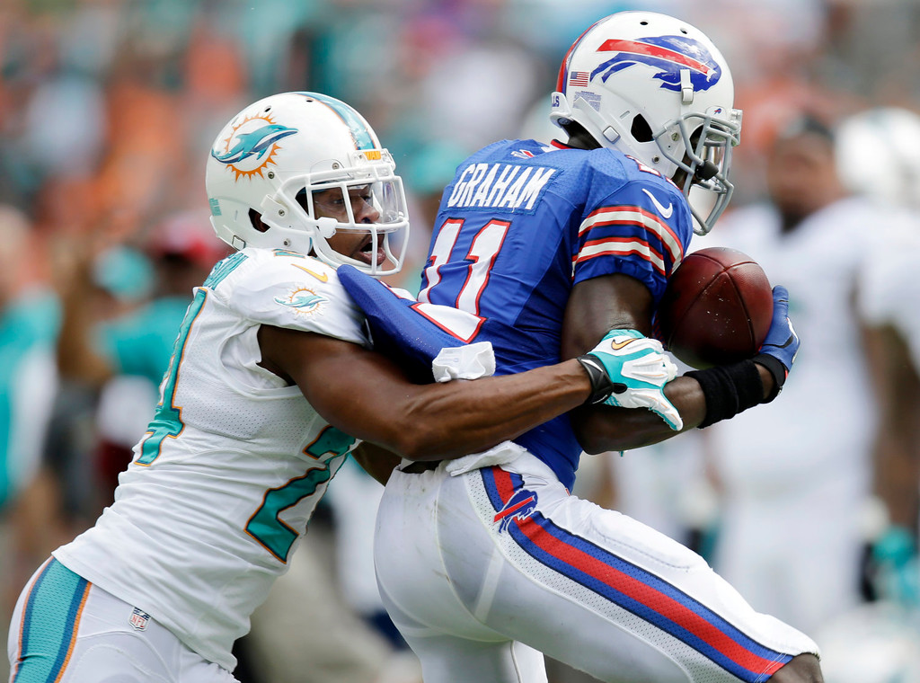 . Miami Dolphins cornerback Dimitri Patterson, left, tackles Buffalo Bills wide receiver T.J. Graham during the first half of an NFL football game Sunday, Oct. 20, 2013, in Miami Gardens, Fla. (AP Photo/Wilfredo Lee)