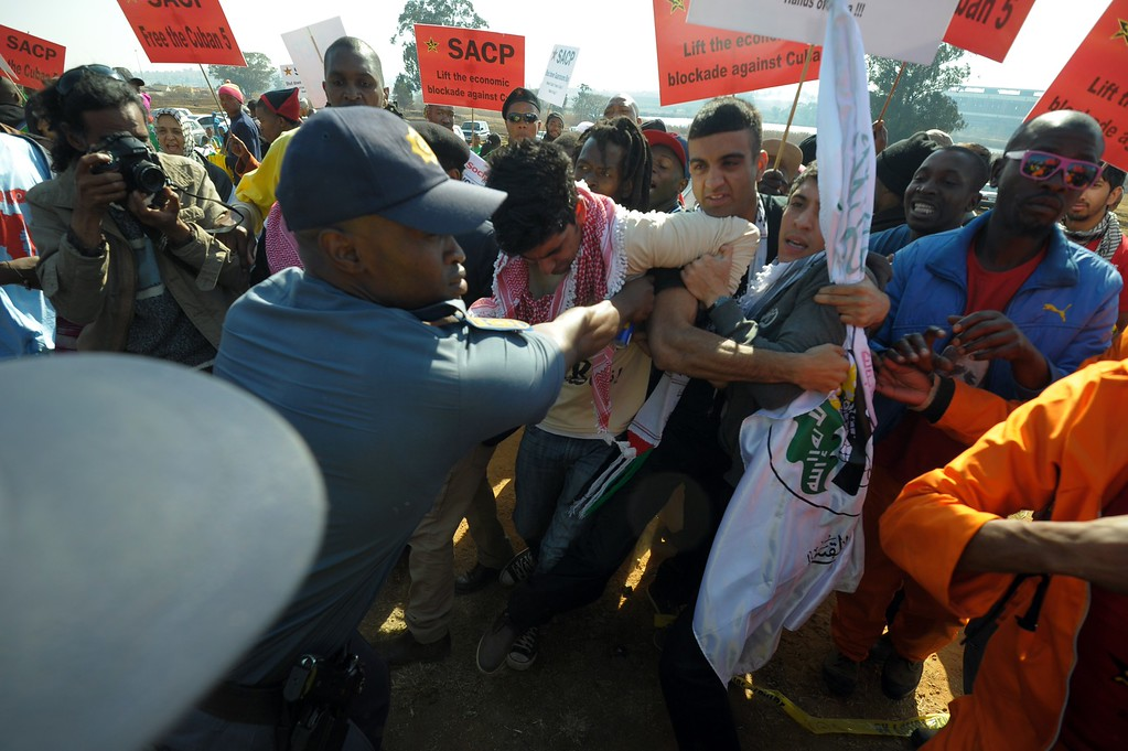 ". Protestors holding Supporters of the South African Communist Party (SACP) signs face police during a demonstration against the visit of the US President in South Africa on June 29, 2013 in Soweto. US President Barack Obama Saturday decided not to visit his political hero Nelson Mandela in hospital to preserve the ""peace and comfort\"" of the anti-apartheid legend, whose family he will meet to offer prayers instead. ALEXANDER JOE/AFP/Getty Images"
