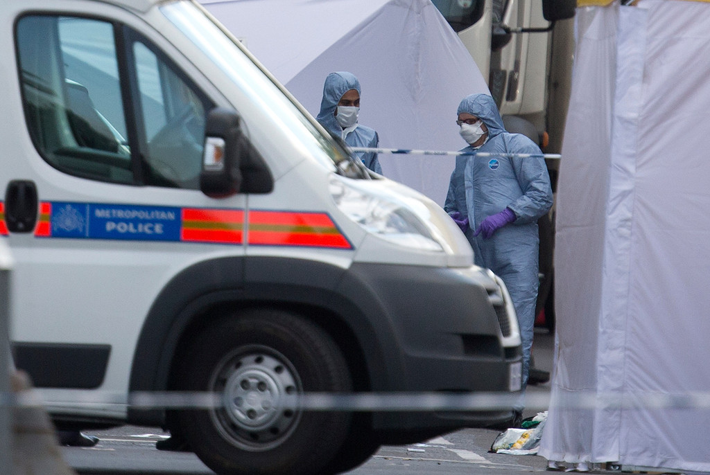 . British forensic officers attend the scene of an apparent attack which has left one man confirmed dead and two people wounded near Woolwich barracks in London Wednesday, May, 22, 2013.  (AP Photo/Alastair Grant)