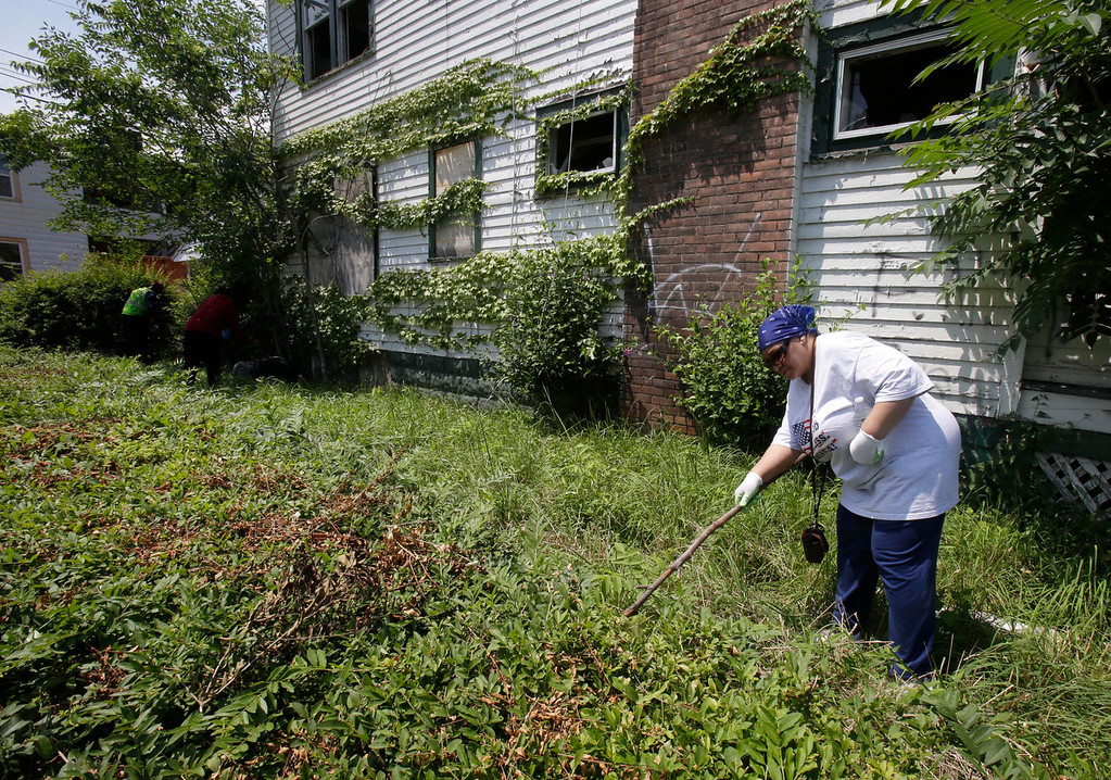 . Fheila McCoy searches bushes outside a abandoned home Sunday, July 21, 2013, in East Cleveland, Ohio. Police Chief Ralph Spotts told volunteers checking vacant houses in a neighborhood where three bodies were found wrapped in plastic bags that he believes there could be one or two more victims. (AP Photo/Tony Dejak)