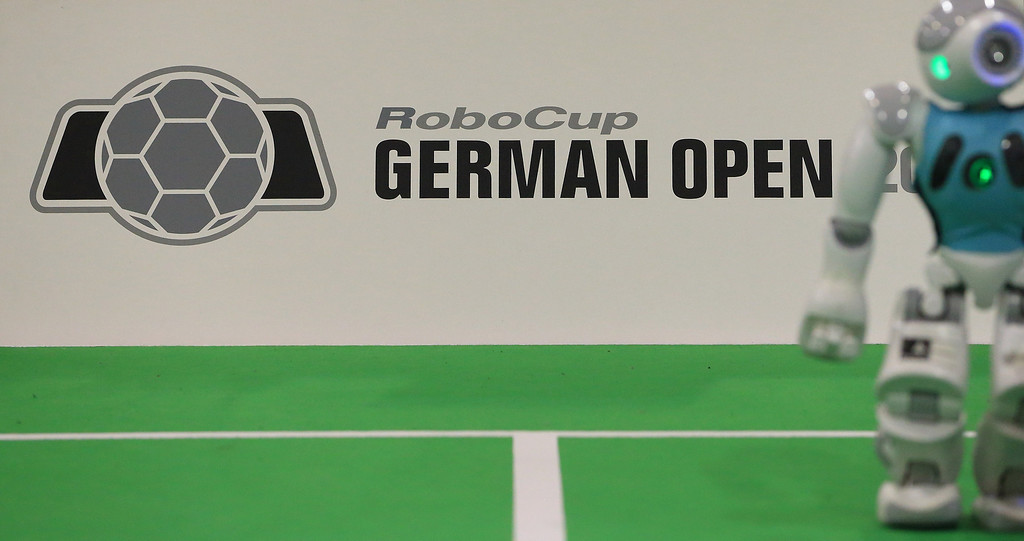 """. A robot stands next to the logo of the \""""RoboCup German Open 2014\"""" in Magdeburg, eastern Germany on April 3, 2014. 950 participants from 12 countries participate in the three-day tournament. The robots are required to master a variety of disciplines, including communication, soccer, rescue and dance.  AFP PHOTO / DPA/ JENS WOLF /AFP/Getty Images"""