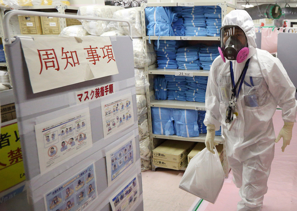 . A worker wearing a protective suit and a mask walks through the Seismic Isolated Building, or command center, at the Fukushima Dai-ichi nuclear power plant in Okuma, Fukushima, northeastern Japan, Thursday, Nov. 7, 2013. (AP Photo/Tomohiro Ohsumi, Pool)