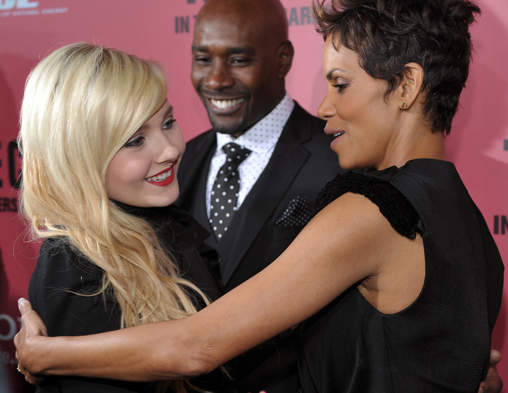 """. Halle Berry, right, and Abigail Breslin, left, cast members in \""""The Call,\"""" greet each other as fellow cast member Morris Chestnut looks on at the world premiere of the film at the Arclight Hollywood on Tuesday, March 5, 2013 in Los Angeles. (Photo by Chris Pizzello/Invision/AP)"""