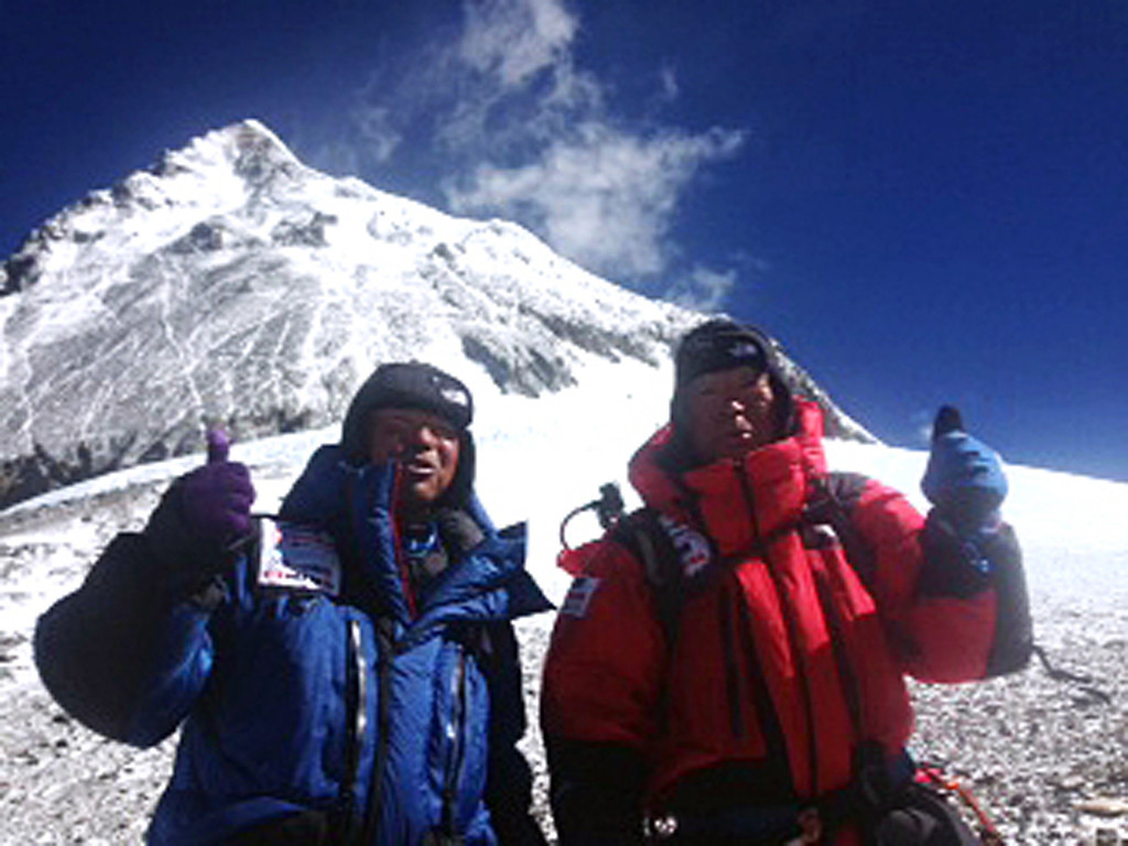 . In this May 22, 2013 photo distributed by Miura Dolphins Co. Ltd., 80-year-old Japanese extreme skier Yuichiro Miura, right, and his son, Gota pose at their South Col camp at 8,000 meters (26,247 feet) before their departure for Camp 5 during their attempt to scale the summit of Mount Everest. Miura, who climbed Mount Everest five years ago, but just missed becoming the oldest man to reach the summit, was back on the mountain Wednesday to make another attempt at the title. (AP Photo/Miura Dolphins Co. Ltd.)  MANDATORY CREDIT
