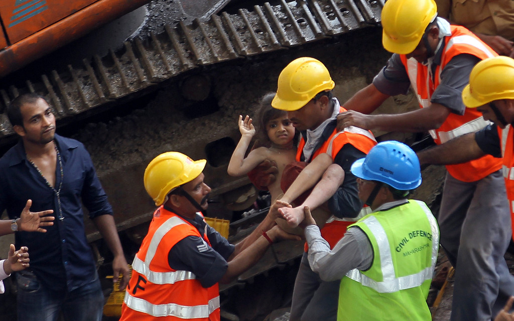 . Rescue workers carry a girl out from the rubble of a building that collapsed in Mumbai, India, Friday, Sept. 27, 2013. The apartment building collapsed in India\'s financial capital of Mumbai early Friday, killing people and sending rescuers racing to reach dozens of people trapped in the rubble. (AP Photo/Rajanish Kakade)