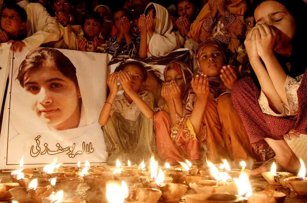 ". Pakistani children pray for the recovery of 14-year-old schoolgirl Malala Yousufzai, who was shot on Tuesday by the Taliban for speaking out in support of education for women, during a candlelight vigil in Karachi, Pakistan, Friday, Oct. 12, 2012. A Pakistani military spokesman says Yousufzai is in ""satisfactory\"" condition but cautions that the next few days will be critical. Writing reads on the poster left, \""Malala Yousufzai.\""  (AP Photo/Shakil Adil)"