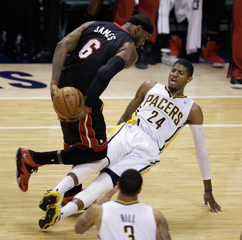 . Miami Heat\'s LeBron James (6) collides with Indiana Pacers\' Paul George during the first half of Game 5 of the Eastern Conference finals NBA basketball playoff series Wednesday, May 28, 2014, in Indianapolis. James was called for a foul. (AP Photo/Darron Cummings)