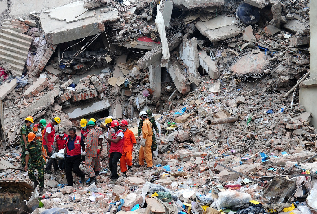 . Members of the Bangladeshi Army carry the body of a garment worker, as heavy equipment is brought in to remove debris following an eight-story building collapse, in Savar on the outskirts of Dhaka on April 30, 2013.  AFP PHOTO/MUNIR UZ  ZAMAN/AFP/Getty Images