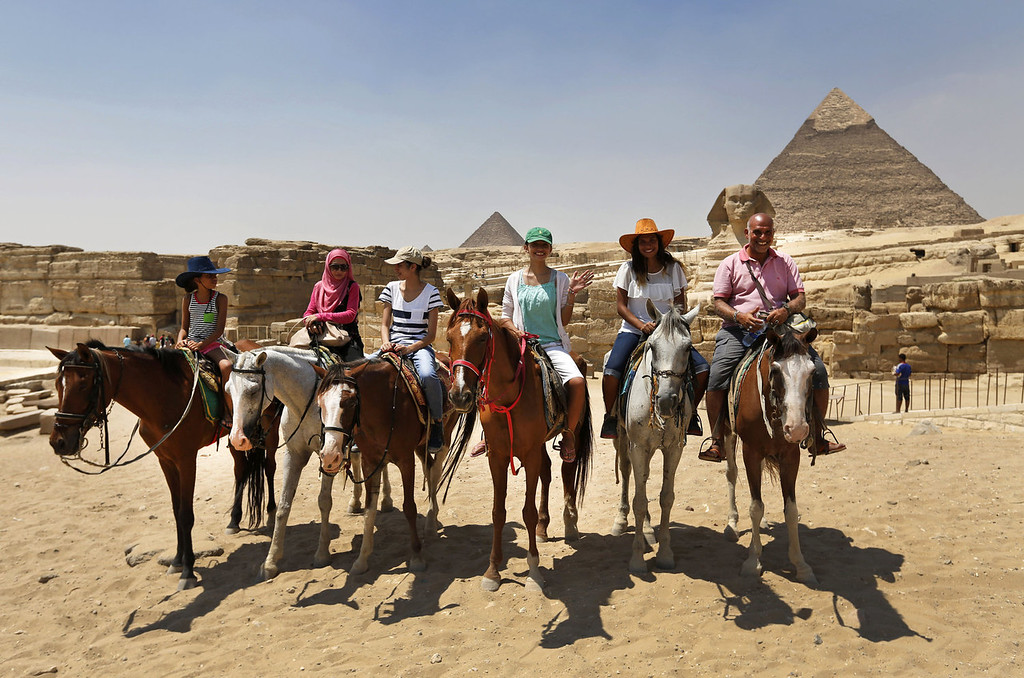 . Visitors horse ride at the the historical site of the Giza Pyramids, background, near Cairo, Egypt, Tuesday, Aug. 27, 2013. The chairman of the Egyptian Airports Co. says some flights are arriving nearly empty to Egypt and that passenger traffic in the past week has fallen by half. Due to the country\'s violent turmoil, some flights that can carry more than 100 passengers from Europe arrive with just nine and return full from beach resorts. (AP Photo/Lefteris Pitarakis)