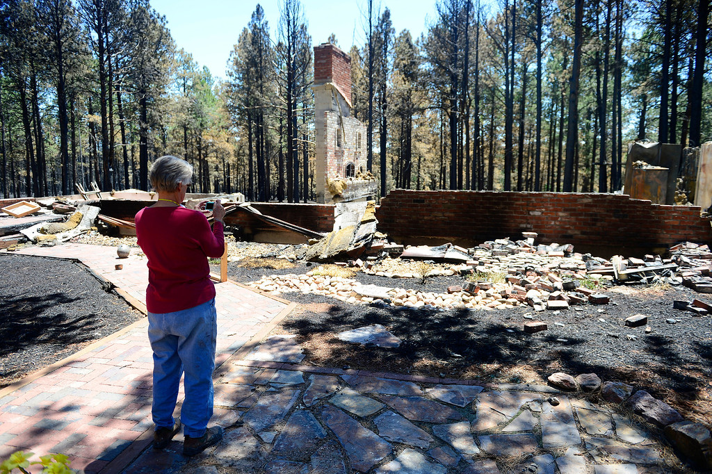 . BLACK FOREST, CO - JUNE 19: Vaneal Burgess takes a picture of her home that was destroyed by the Black Forest Fire on Shoup Road. Burgess, and her husband, Don, owned the home for 35 years, raised their children and entertained their 13 grandchildren. Their daughter also lost her home to the Black Forest Fire near Herring Road. (Photo by AAron Ontiveroz/The Denver Post)