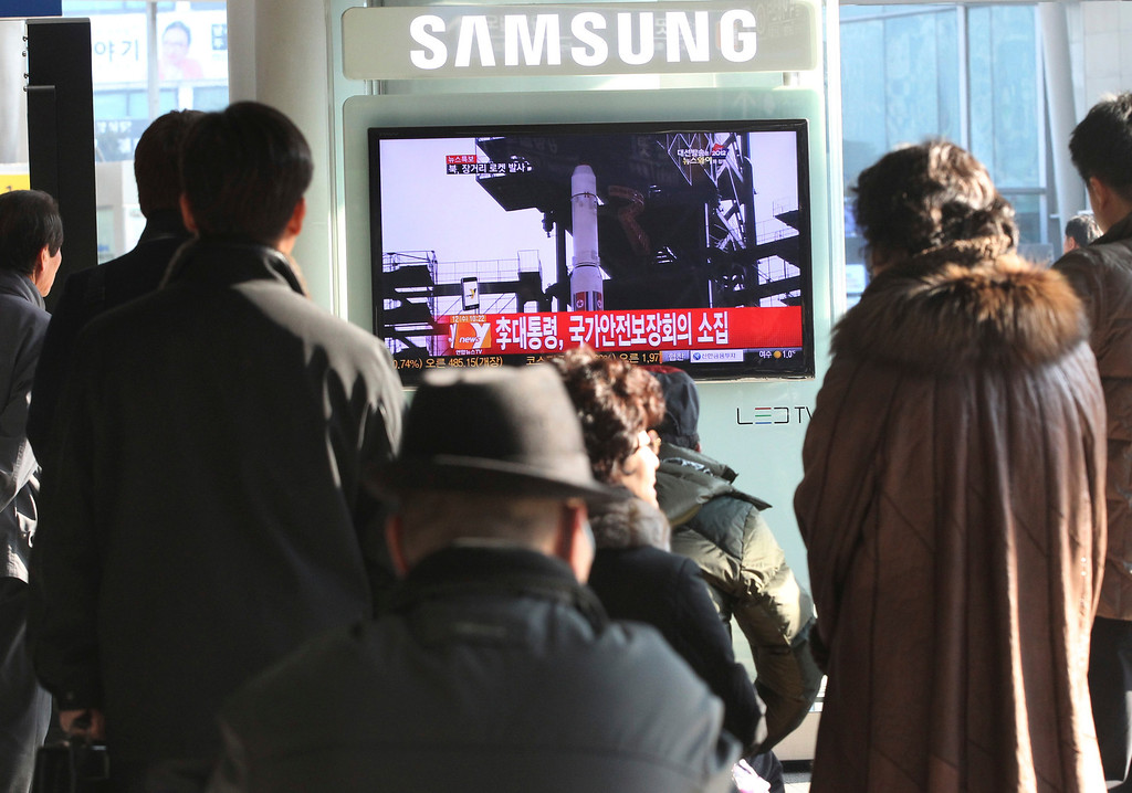 """. South Koreans watch public TV reporting a news about North Korea\'s rocket launch at Seoul Railway Station in Seoul, South Korea, Wednesday,  Dec. 12, 2012. North Korea fired a long-range rocket Wednesday in its second launch under its new leader, South Korean officials said, defying warnings from the U.N. and Washington only days before South Korean presidential elections. The letters on the screen read \""""  President Lee Myung-bak convened an emergency meeting of the National Security Council. \"""" (AP Photo/Ahn Young-joon)"""