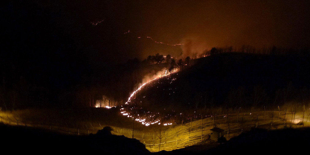 . A blaze is seen in the demilitarized zone (DMZ) separating North Korea and South Korea, in this picture taken from just south of the DMZ in Goseong, about 330 km (205 miles) northeast of Seoul April 13, 2013. The blaze, first spotted in the northern side of the 4-km-wide DMZ on Saturday, spread and reached within 100 meters of the nearest South Korean guard posts inside the DMZ, Yonhap reported. The cause of the fire is unknown. Picture taken April 13, 2013.   REUTERS/Goseong County Office/Handout