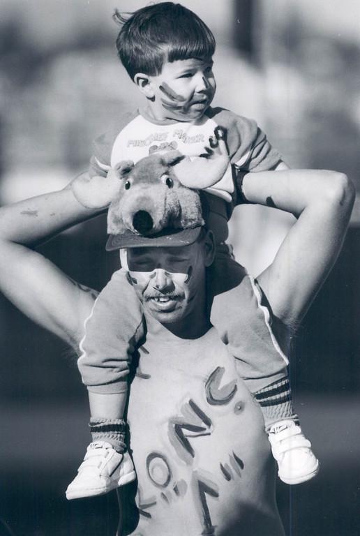 . 1/25/1988 - San Diego, Jan. 25 - Wait Harris  and his sone Chris, 2, watching the Denver Broncos arrive Monday in San Diego. (Damien Strohmeyer/The Denver Post)