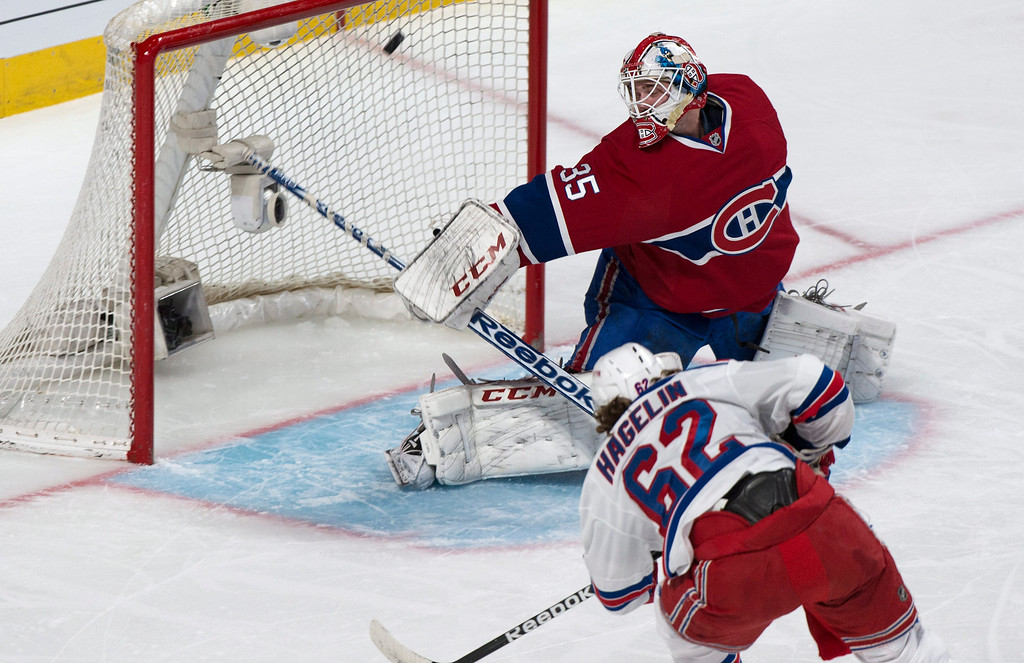 . Montreal Canadiens goalie Dustin Tokarski deflects a shot by New York Rangers\' Carl Hagelin during the first period of Game 5 of the NHL hockey Stanley Cup playoffs Eastern Conference finals, Tuesday, May 27, 2014, in Montreal. (AP Photo/The Canadian Press, Paul Chiasson)