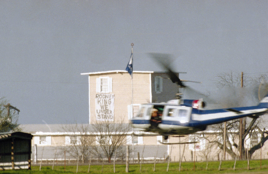 . A military helicopter buzzes past the Mount Carmel Branch Davidian compound in Waco, Texas on Friday, March 27, 1993. The standoff between law enforcement and the Branch Davidian cult continues in the 27-day. The FBI said they have not talked with cult leader David Koresh since Wednesday night. (AP Photo/David Phillip)