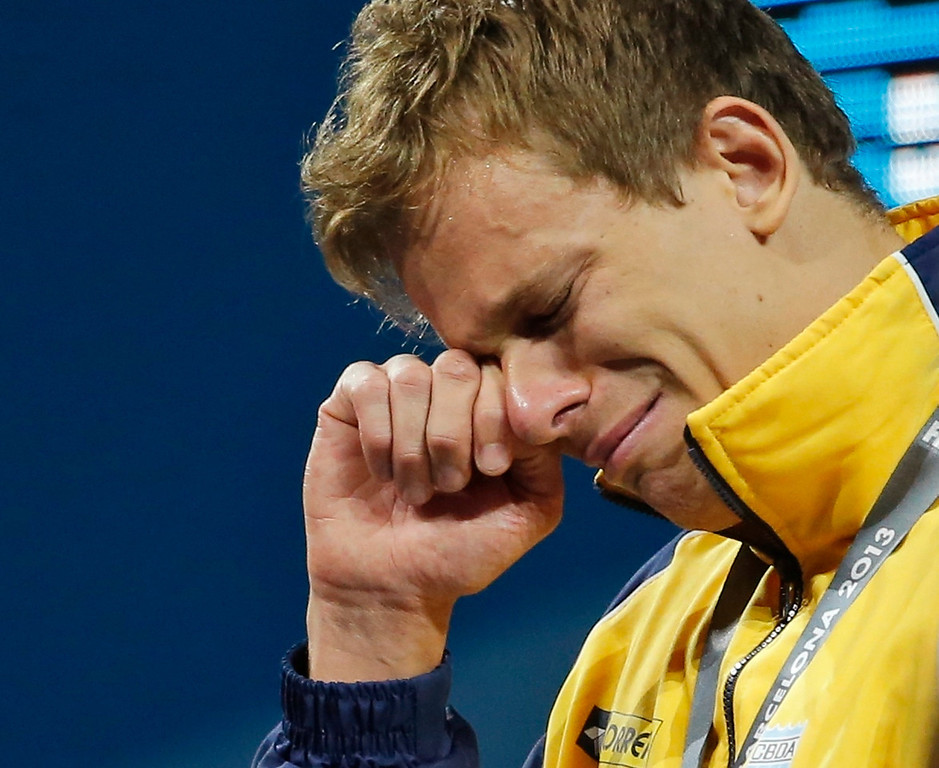 . Brazil\'s Cesar Cielo Filho wipes away tears after receiving his gold medal during the presentation ceremony for the Men\'s 50m freestyle final at the FINA Swimming World Championships in Barcelona, Spain, Saturday, Aug. 3, 2013. (AP Photo/Daniel Ochoa de Olza)