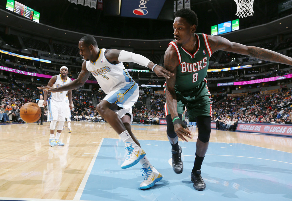 . Denver Nuggets forward J.J. Hickson, left, scrambles after a loose ball with Milwaukee Bucks center Larryt Sanders in the first quarter of an NBA basketball game in Denver, Wednesday, Feb. 5, 2014. (AP Photo/David Zalubowski)